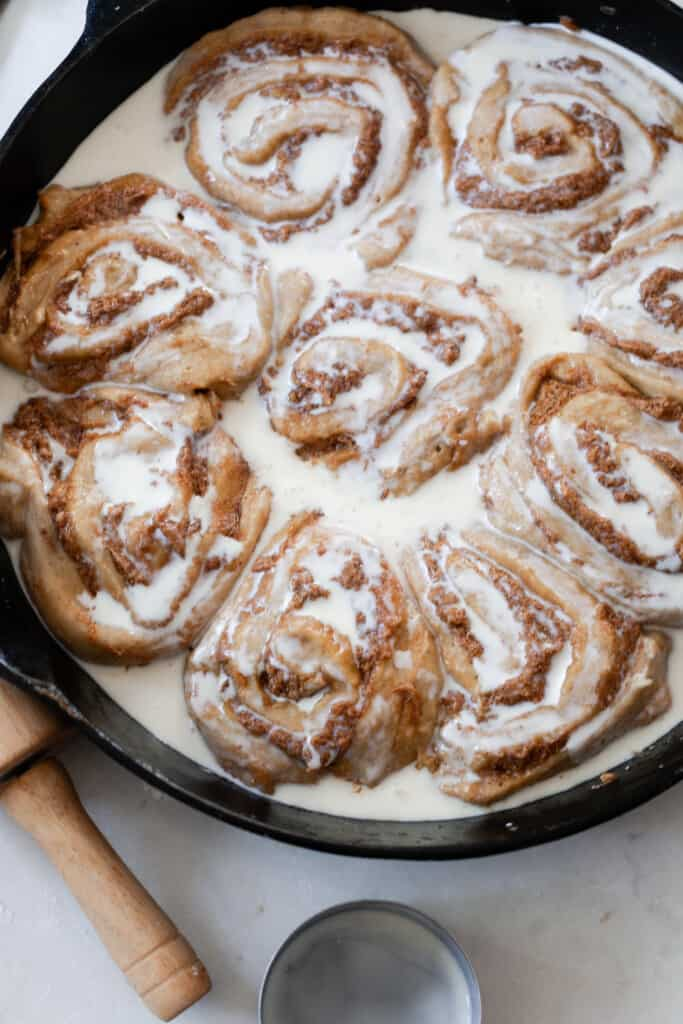 cream poured over raw sourdough pumpkin cinnamon rolls in a cast iron skillet on a white countertop with a rolling pin handle to the left