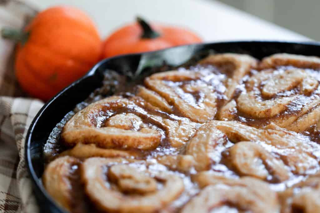 sourdough pumpkin cinnamon roll in a cast iron skillet right out of the oven with two small pumpkins in the background