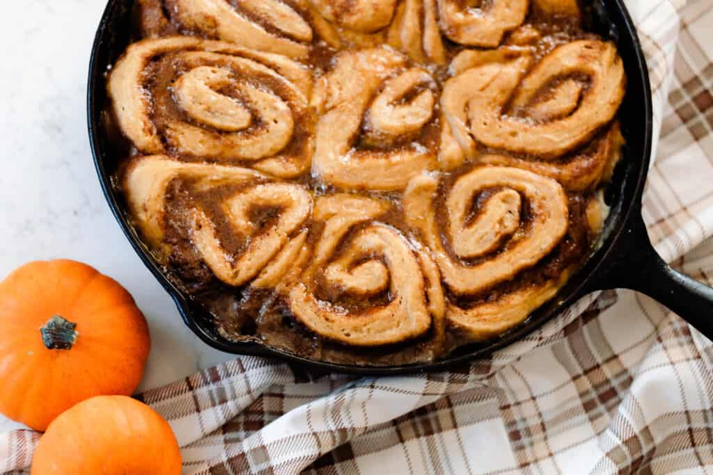 sourdough pumpkin cinnamon rolls baked in the oven on a cream and brown plaid napkin with two small orange pumpkin to the left