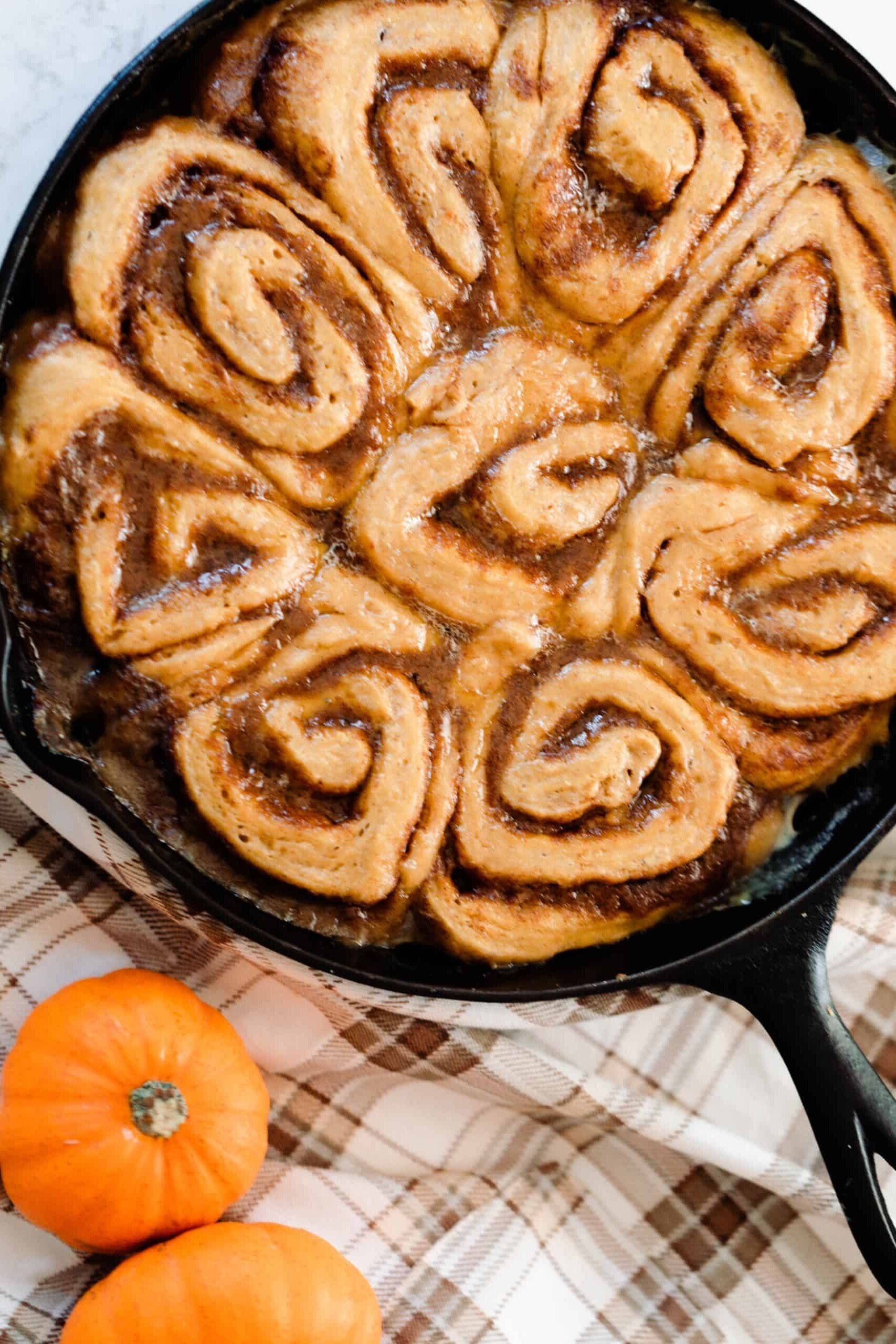 sourdough pumpkin cinnamon rolls in a cast iron skillet on a brown plaid napkin with two small pumpkins to the right