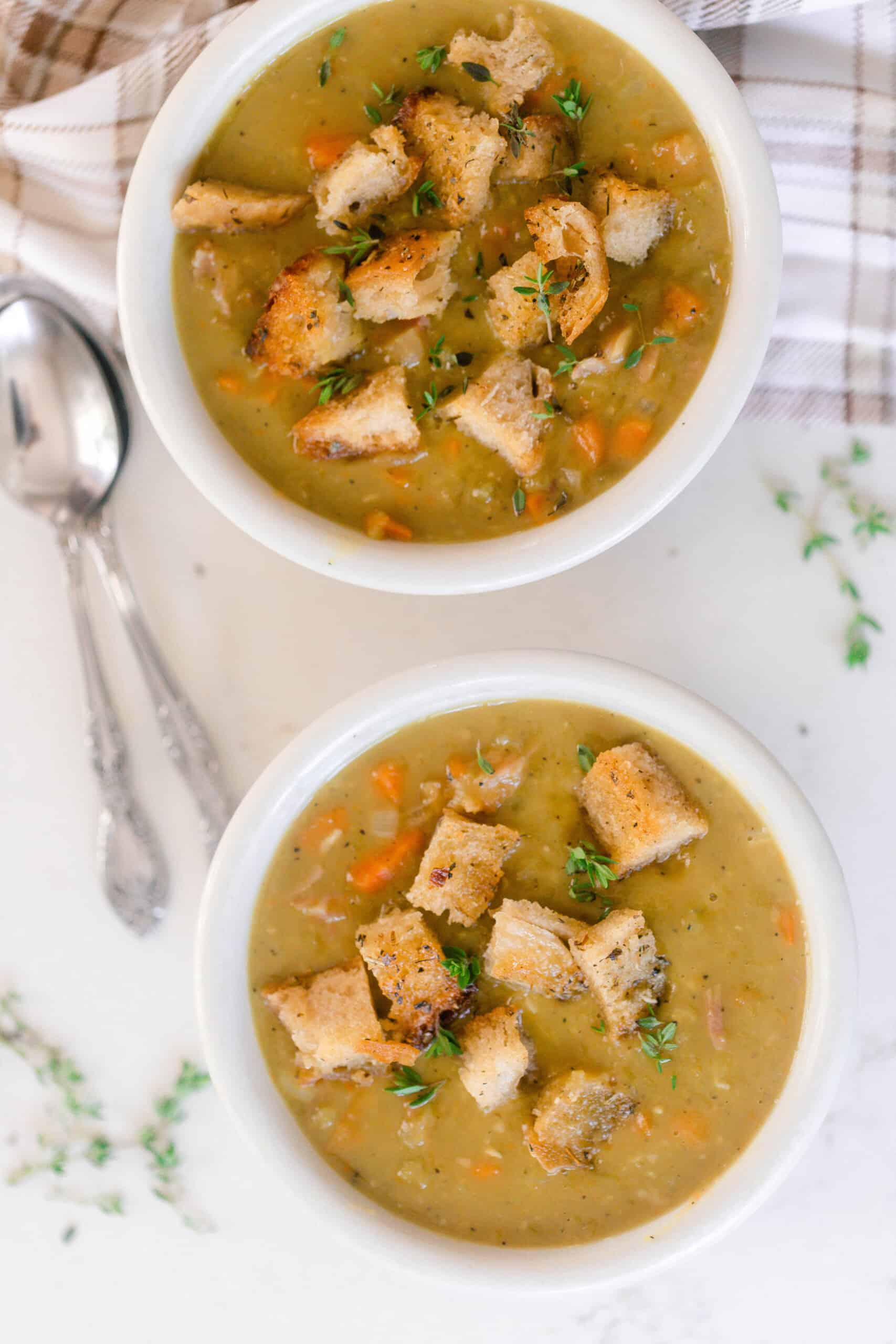 overhead photo of two bowls of homemade split pea soup topped with thyme and sourdough croutons on a white countertop and two spoons to the left and a plaid towel in the top right corner.