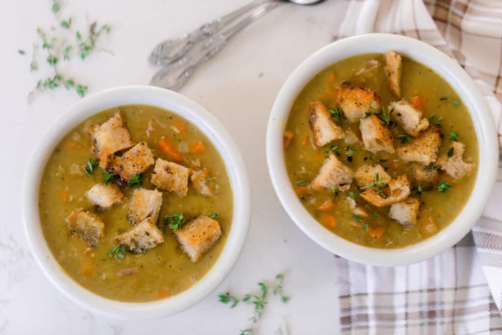 overhead photo of two bowls of ham and pea soup topped with croutons and thyme on a white countertop. One bowl is resting on a brown plaid napkin