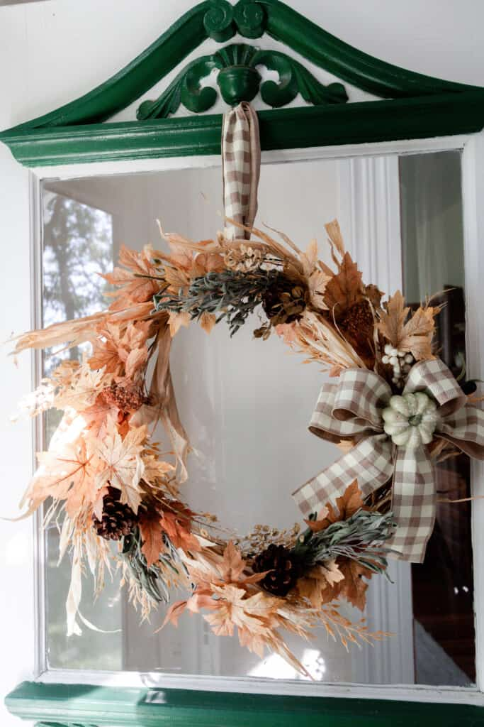 fall inspired wreath with dried leaves, and wheat with a tan and white bowl hanging out a green and white door with glass