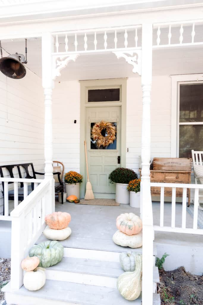 victorian farmhouse front porch with pumpkin stacked on the stairway, mums in crocks by the door and a dried wreath on the front door