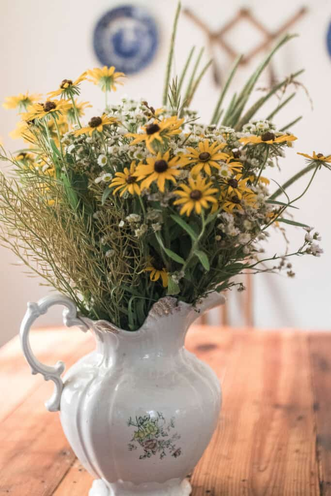 Wildflowers in a vintage pitcher on a wooden table