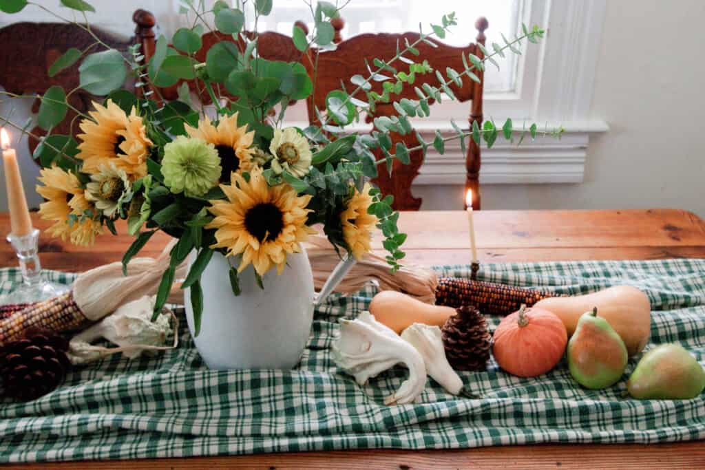 close up picture of a white pitcher full of sunflowers, wild flowers, and eucalyptus on a green plaid table runner with pumpkins and gourds on the table