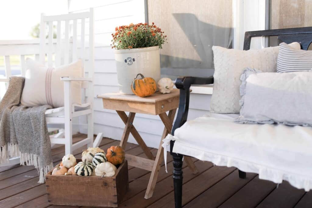 a small wooden table with a crock of mums and a pumpkin on top next to a wooden chair on a porch