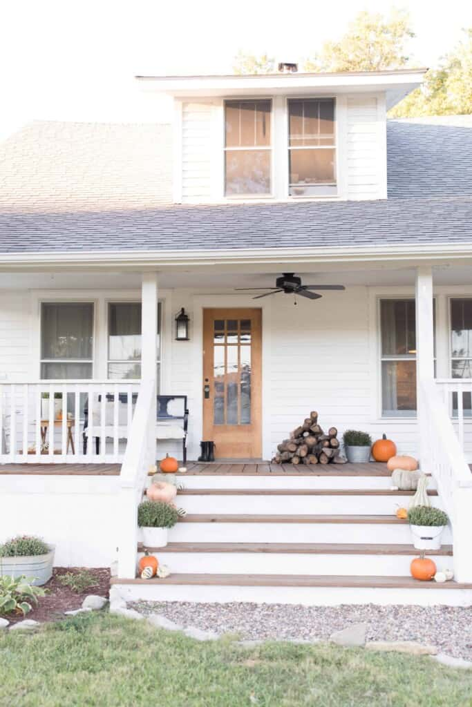 fall farmhouse front porch with pumpkins up the stairway and wood stacked next to the door.