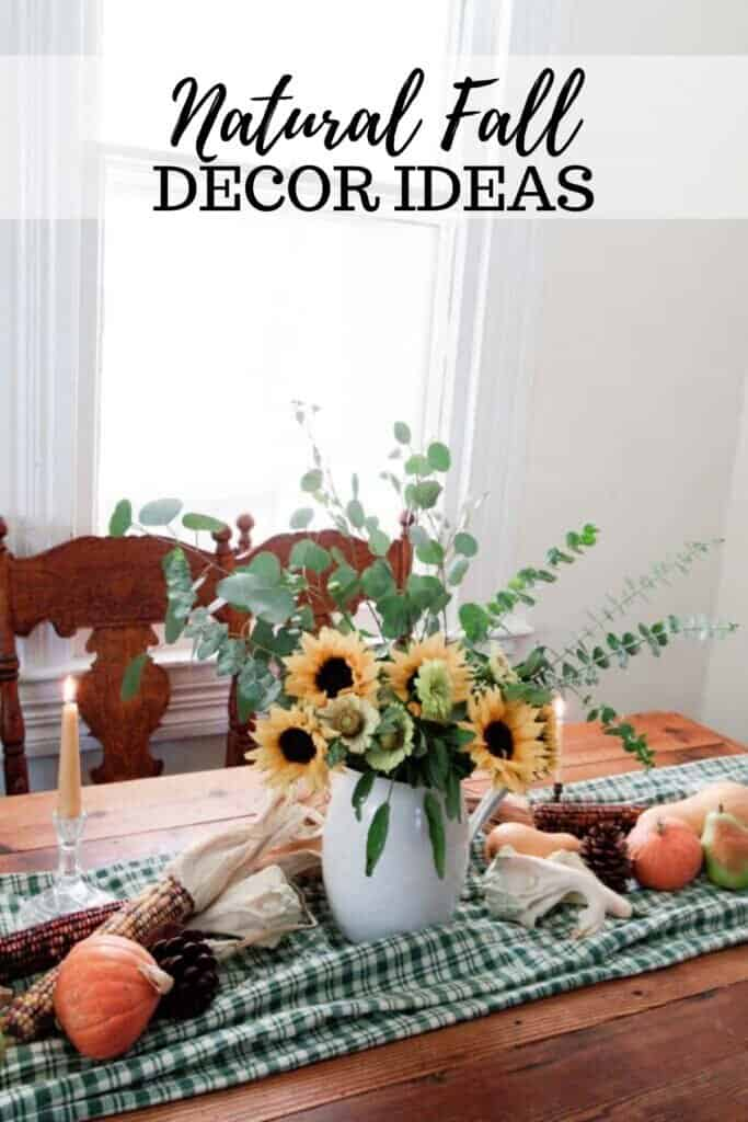 a vintage wood table with a green checked table runner topped with pumpkins, Indian corn, and a vase full of eucalyptus and sunflowers
