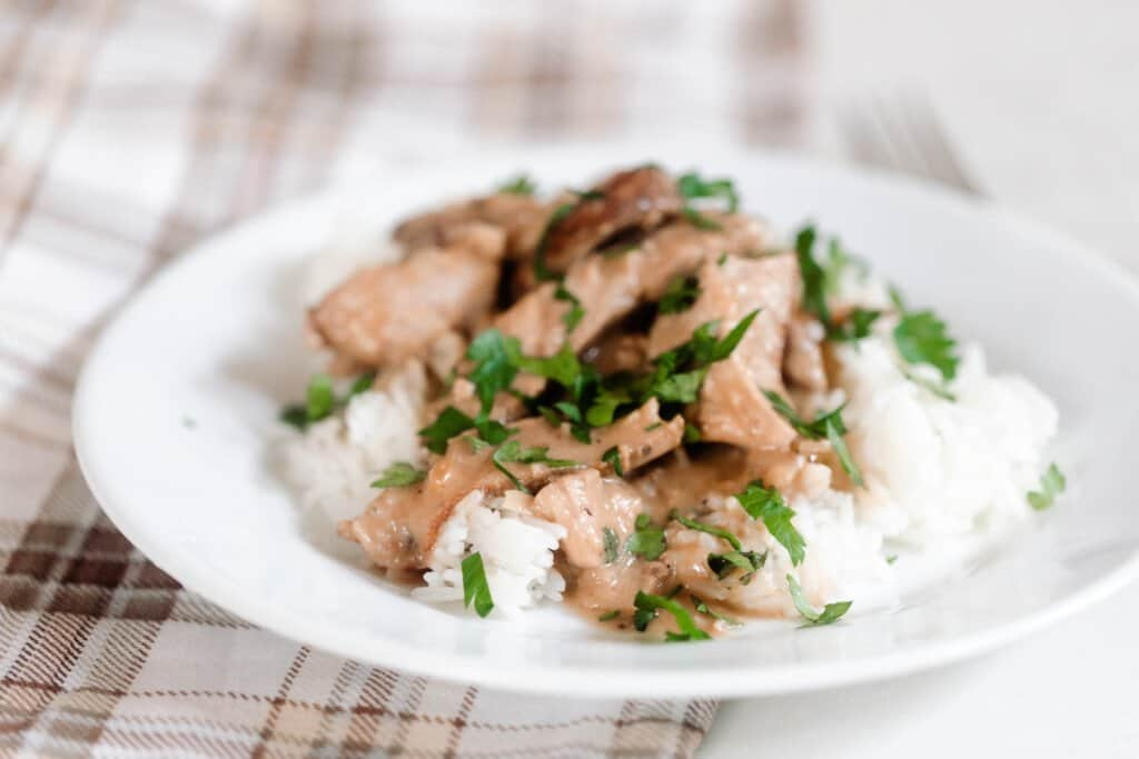 A brown and cream plaid towel with a white plate with rice, sliced pork steak drizzled with a cream sauce and topped with fresh parsley.
