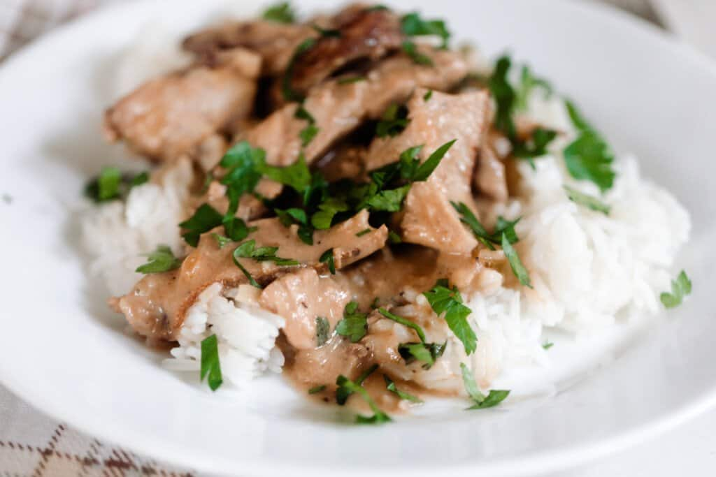 white plate with white rice, pork steak sliced and covered in a cream sauce