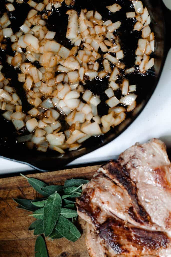 onions caramelized in a cast iron skillet on a stove. A cutting board with pork steaks and parsley