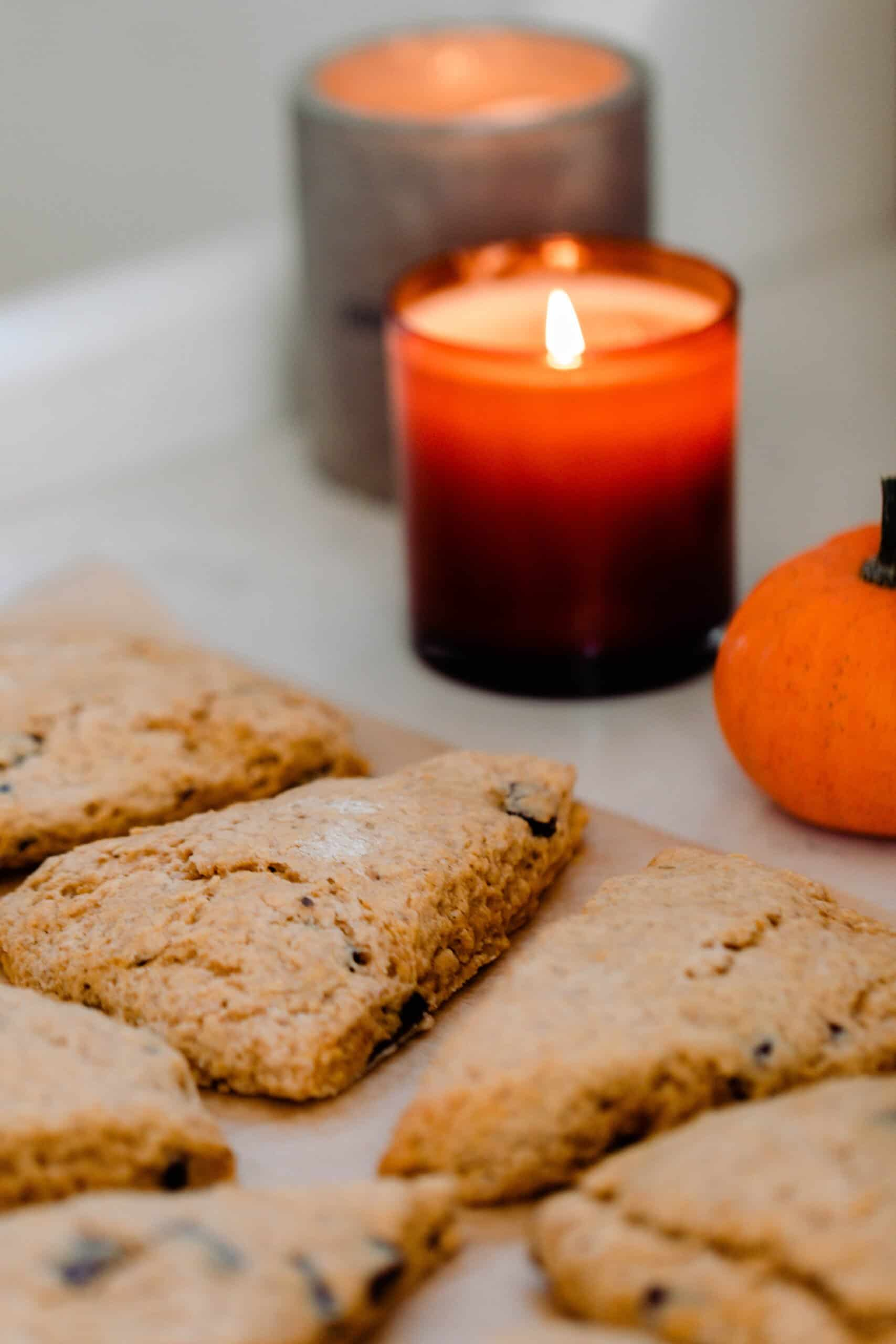sourdough pumpkin scones cut into triangles on a quarts counter top with lit candles in the background
